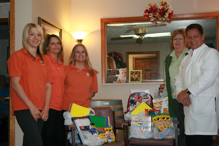 Group photo of employyes with schools supplies that they donated to the C.O.P.E. House for local kids.